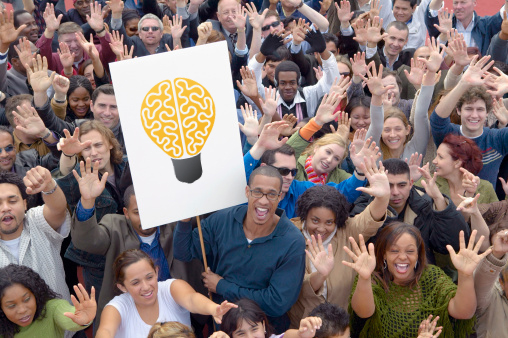 Crowd with lightbulb sign demonstrating the thinking behind marketing strategy.